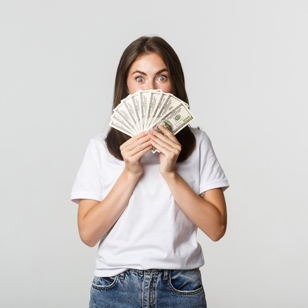 Excited pretty young woman holding money over face, standing white background.